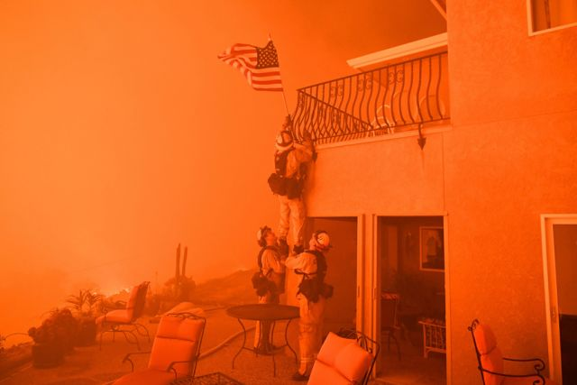 """Firefighters remove a U.S. flag as flames from the """"Wall Fire"""" close in on a luxury home in Oroville, California"""