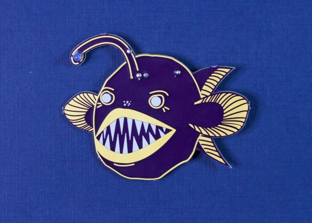 angler fish shaped printed circuit board on a blue background