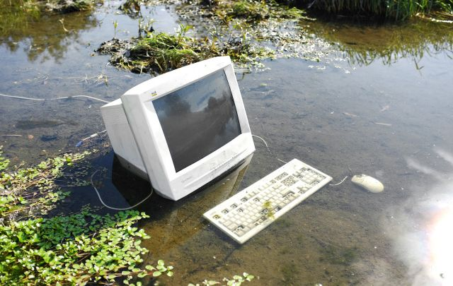 An old desktop monitor and keyboard are posed in a shallow dirty, muddy pond
