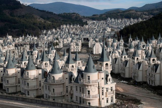 Photograph of a valley in Turkey with dozens of distasteful small mansions looking like castles, all looking exactly the same and placed next to each other