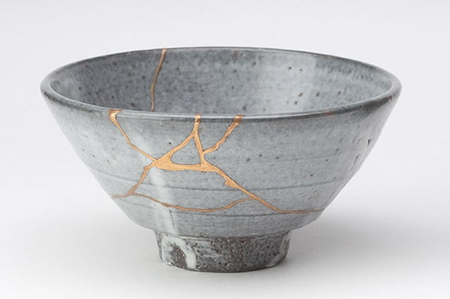 Photograph of a broken grey bowl, reconstructed with cracks filled with gold and resin, forming a noticeable pattern of streams