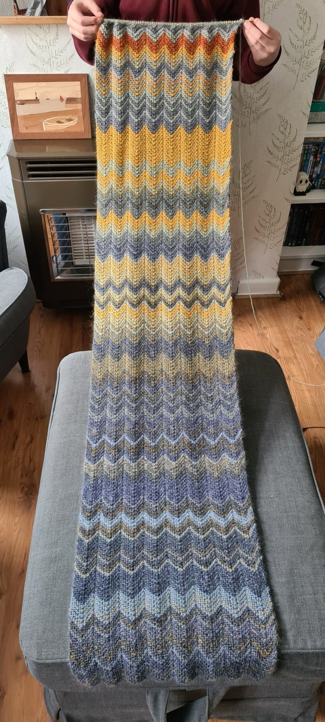 A long hand-knit scarf with rows of alternating colours and materials, going from grey and blue for the winter days to more recent yellows and reds
