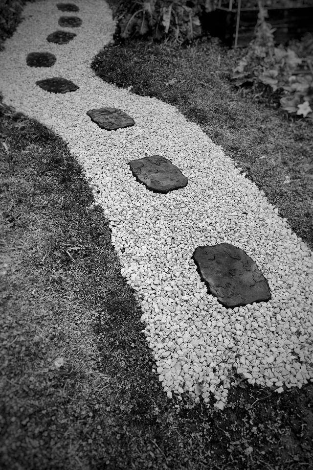 A garden path with dark stepping stones running through it