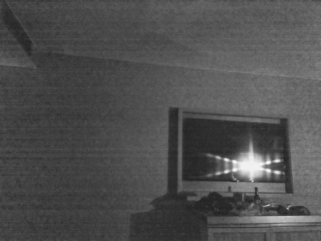 A less fuzzy monochrome photo of a TV in a hotel room.