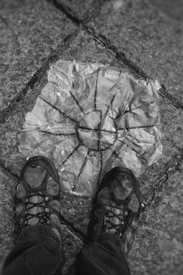 My feet, holding on to a bit of plastic sheet with lines in the shape of a sun on it