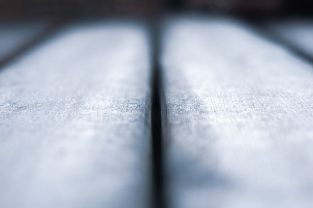 Macro photo, close up of frost on wooden planks receding into the distance