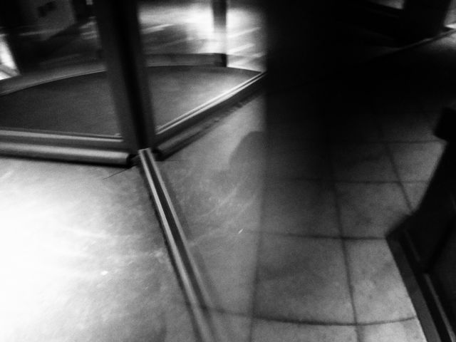 Black and white abstract photo involving a revolving door